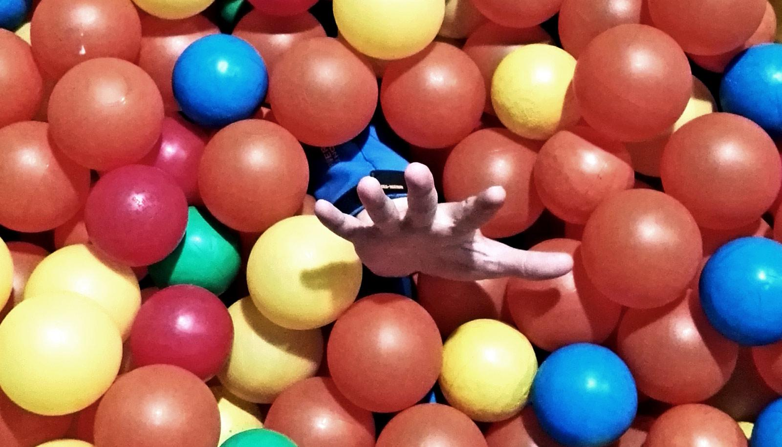 hand coming out of plastic ball pit