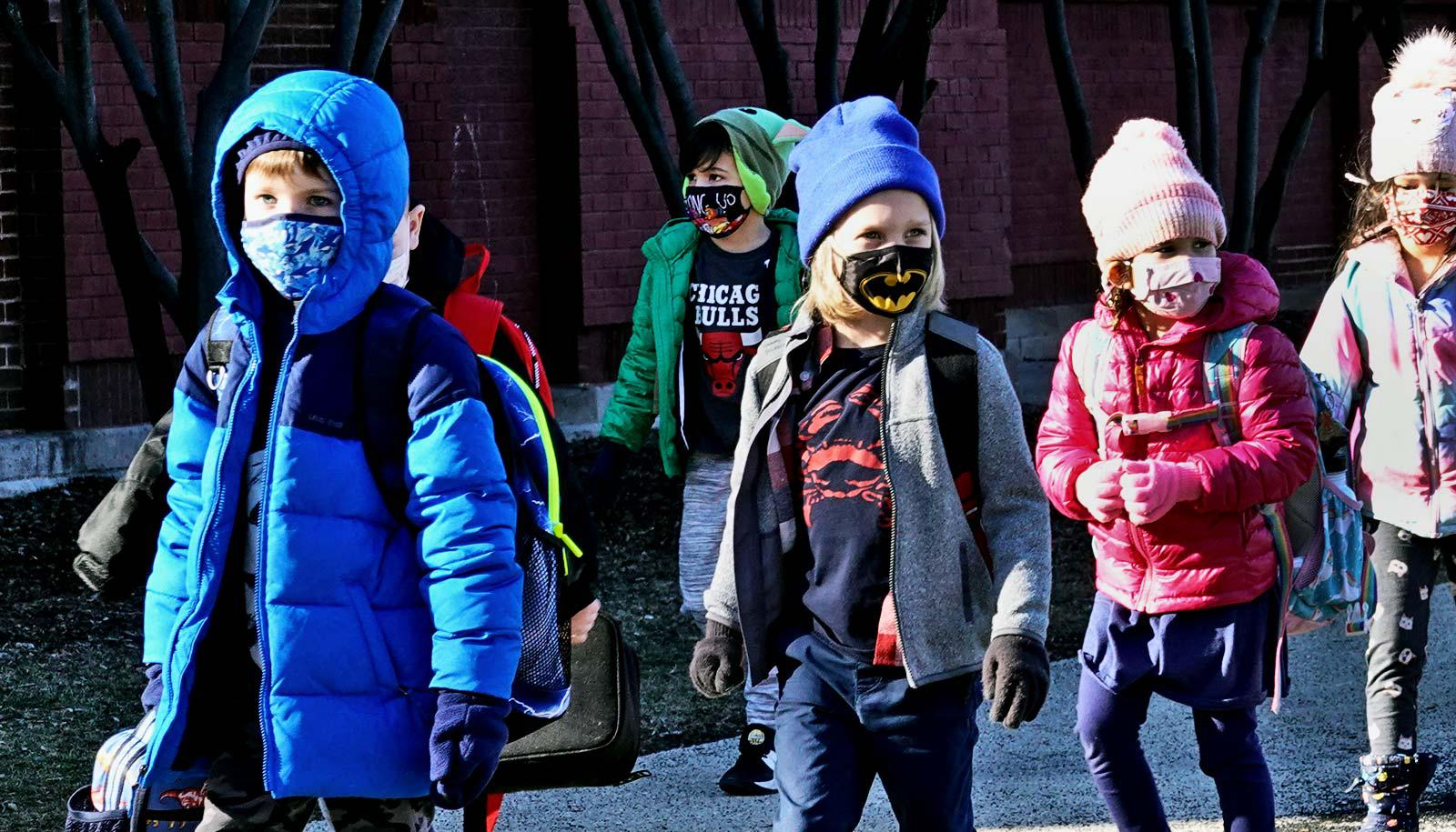 A line of schoolchildren walk with face masks and winter clothing