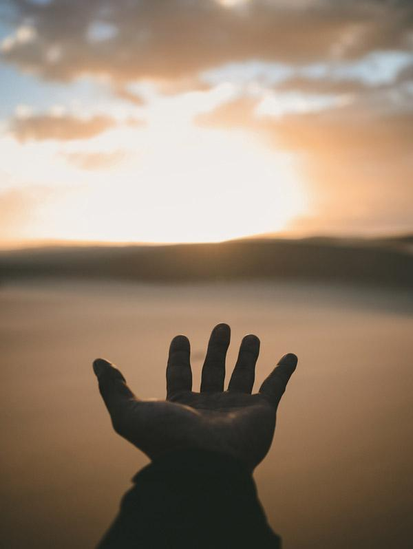 Sharing Your Light, Service to Others. Photograph of hand and sky by Billy Pasco