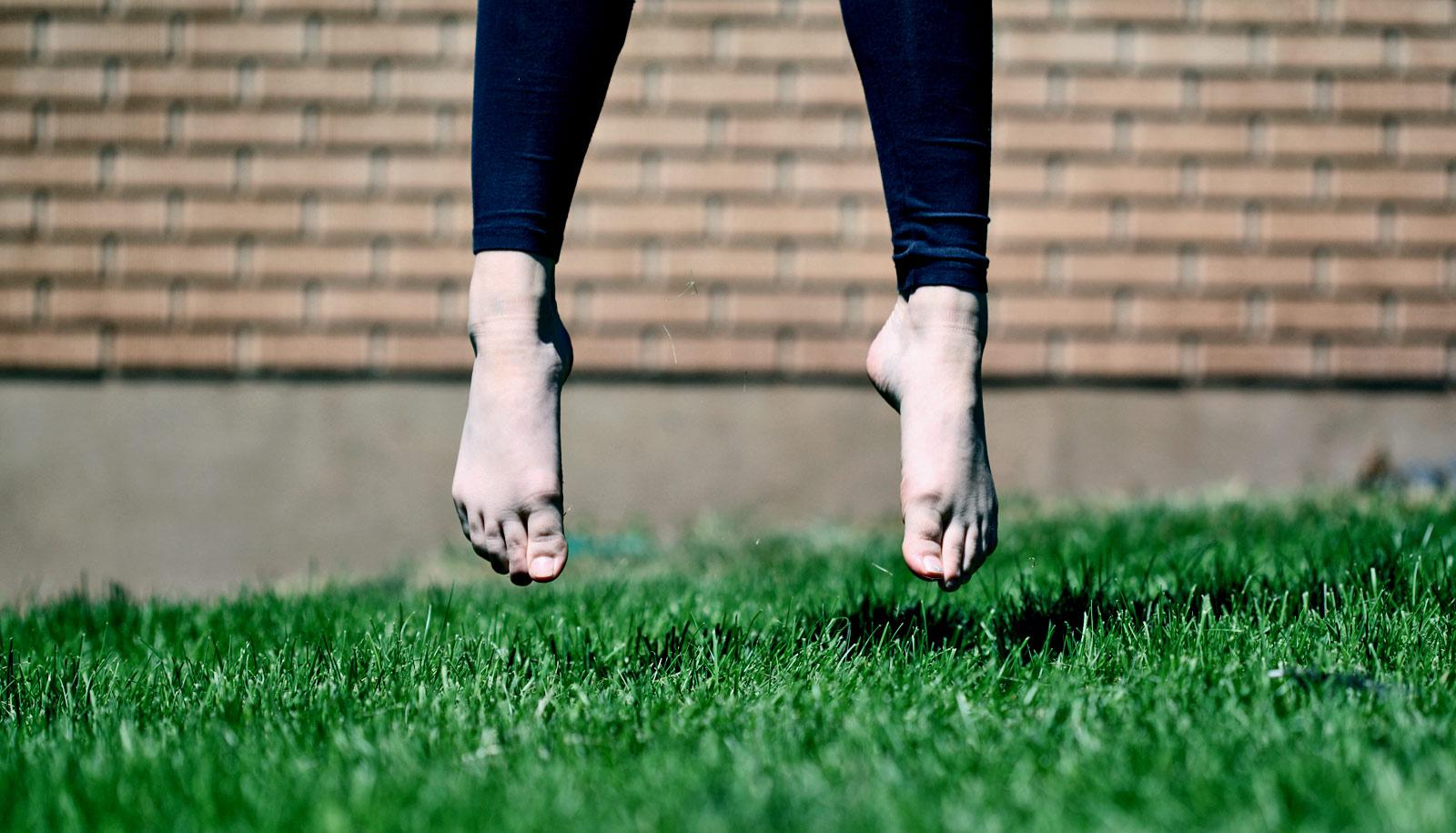 feet of jumping person on grass - human evolution concept