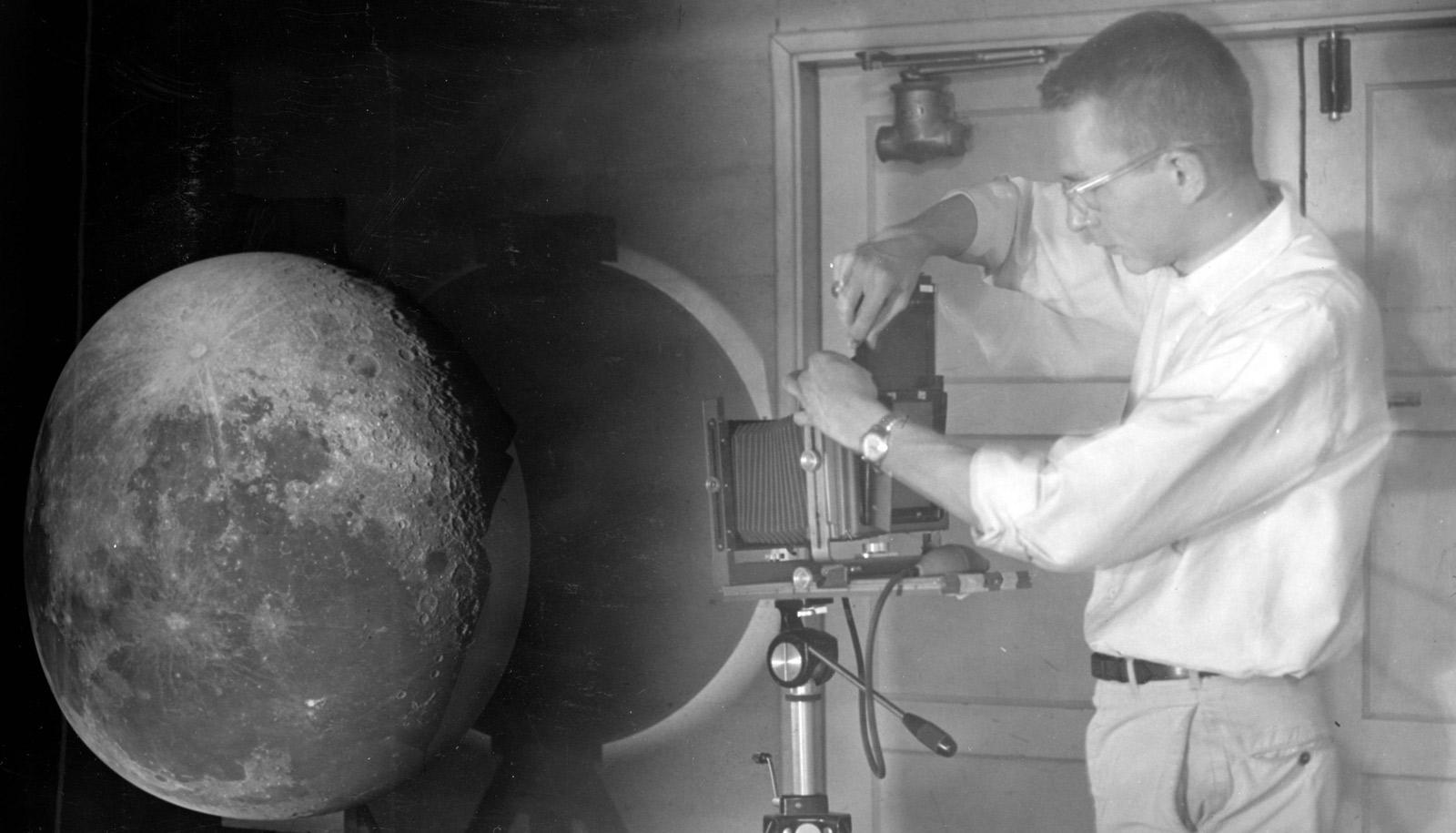 man stands to right of projector with moonscape on sphere