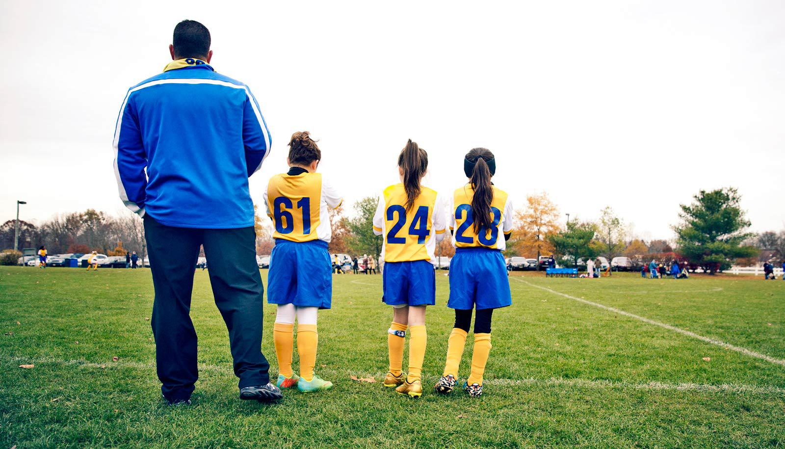 coach and three girls on edge of soccer field