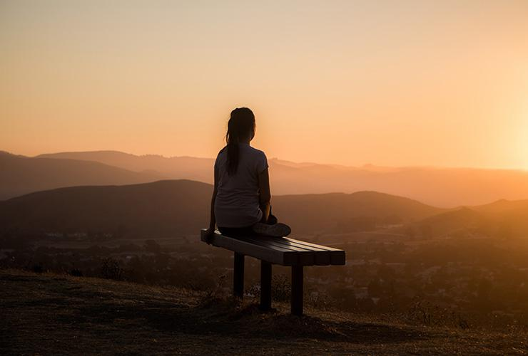 BE STILL: The Power of Stillness & Silence by Amisha Ghandiali. Photograph of a woman sitting on a mountain top at sunset by Sage Friedman
