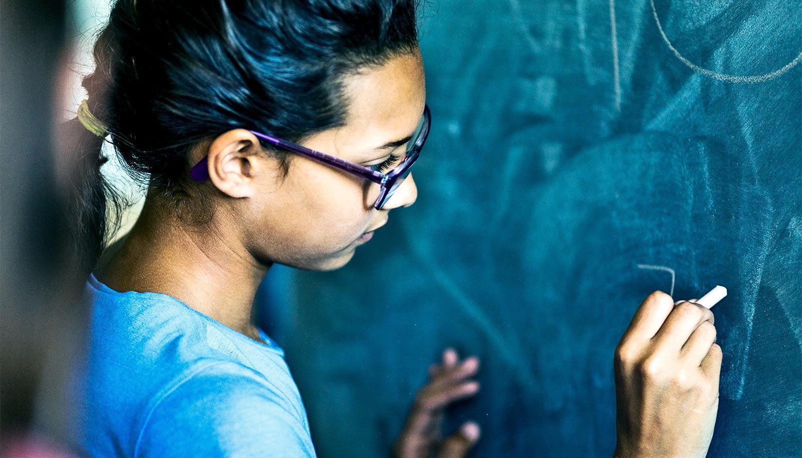 young girl at blackboard