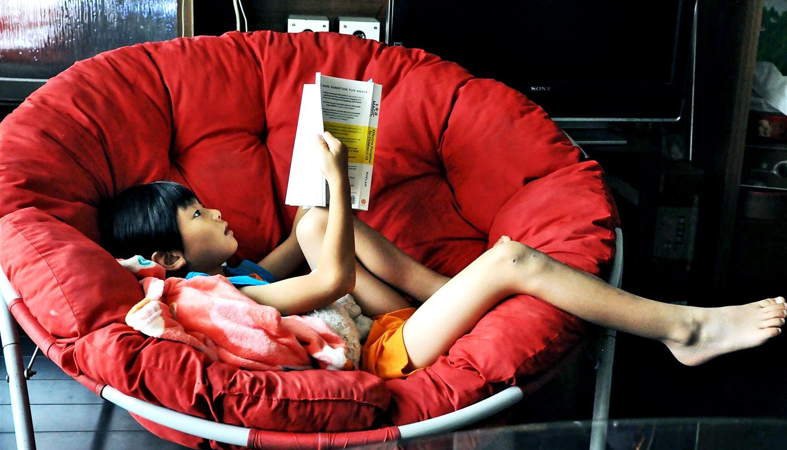 kid reading in red chair (dyslexia concept)