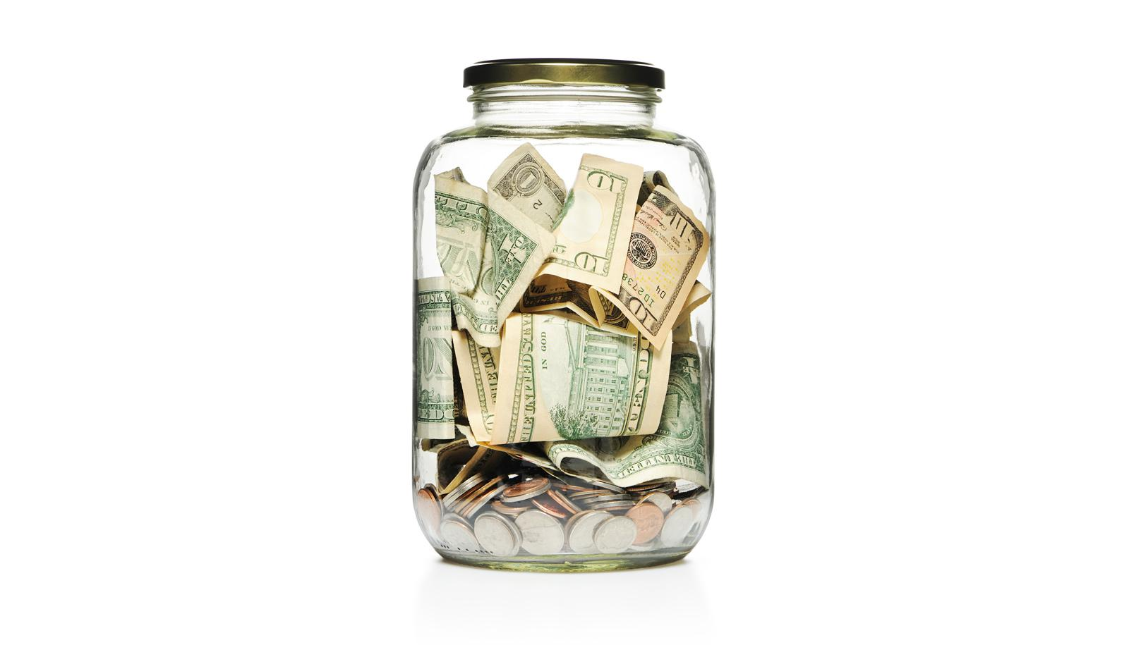 charity - glass jar of paper money and coins