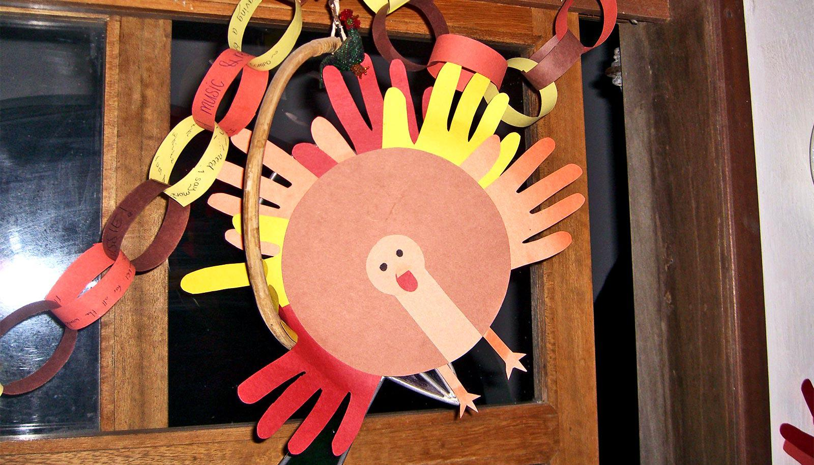 A paper turkey made with outlines of hands cut from colorful paper hangs in a doorway
