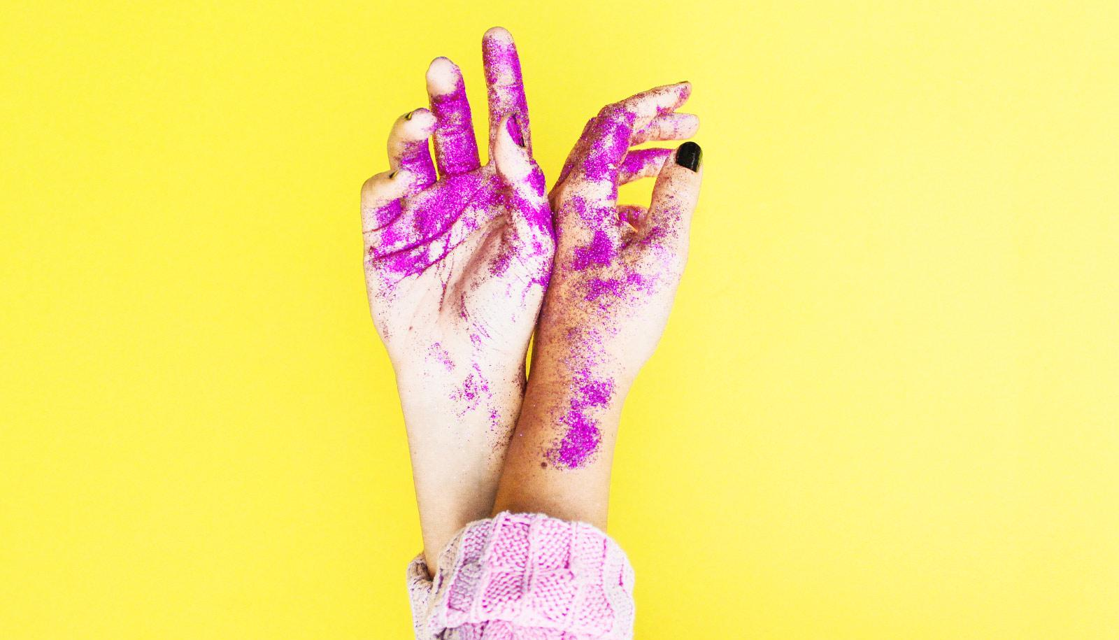 pink glitter on hands against yellow