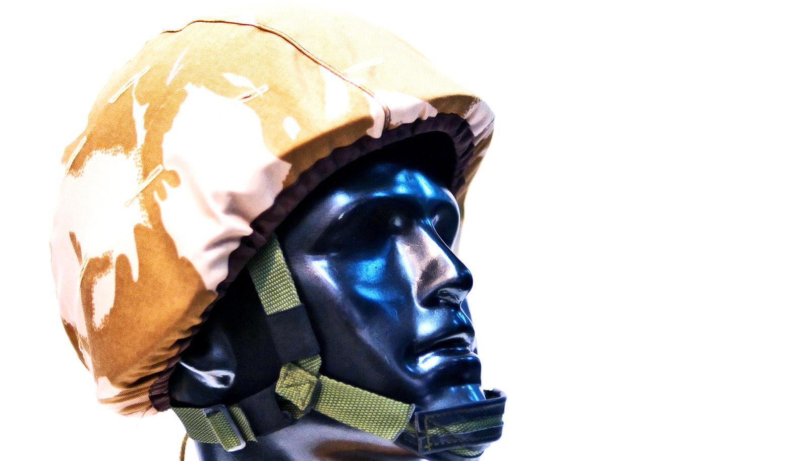A mannequin wears a military-style helmet against a white background