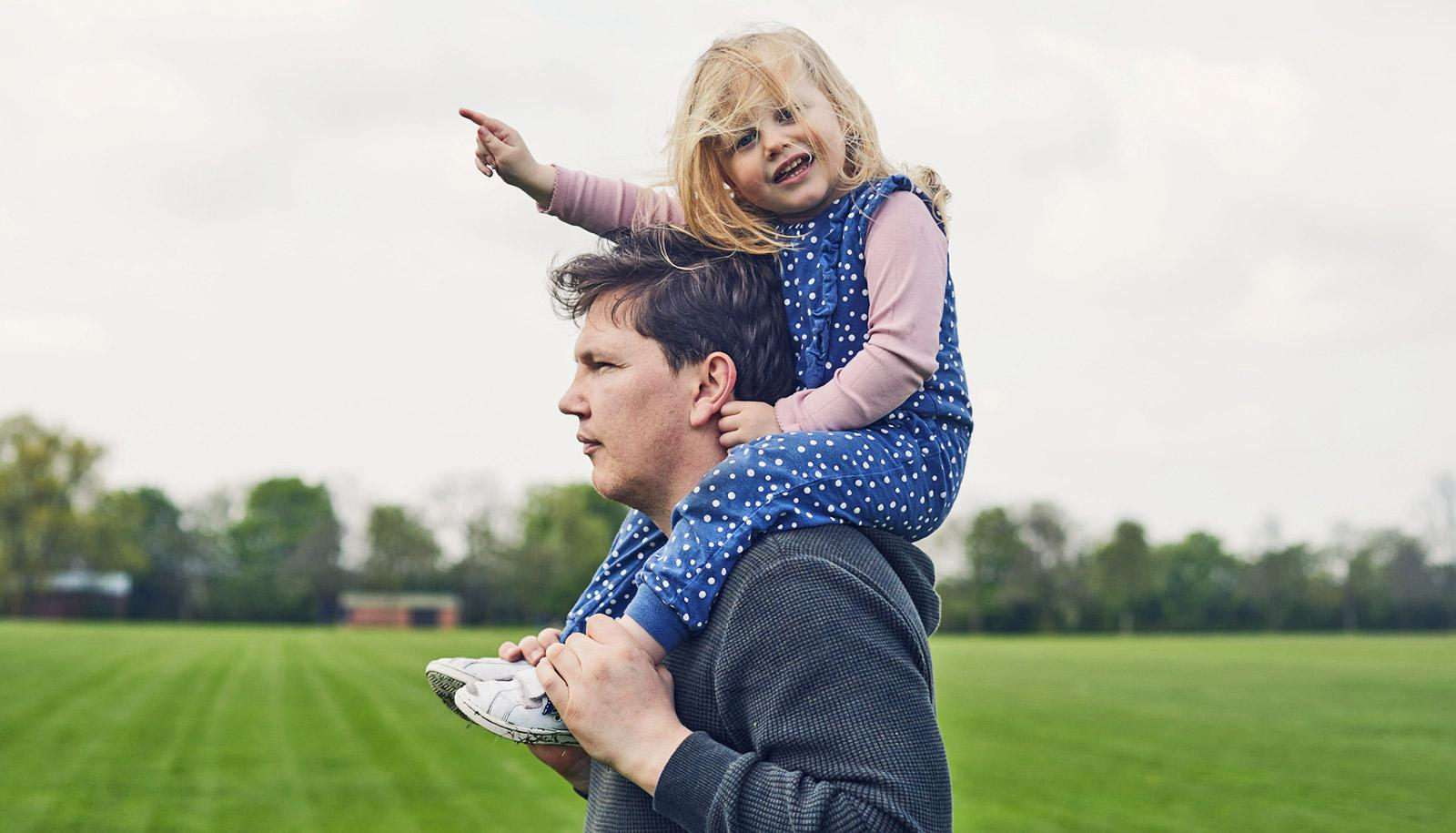 pointing toddler on stoic adult's shoulders