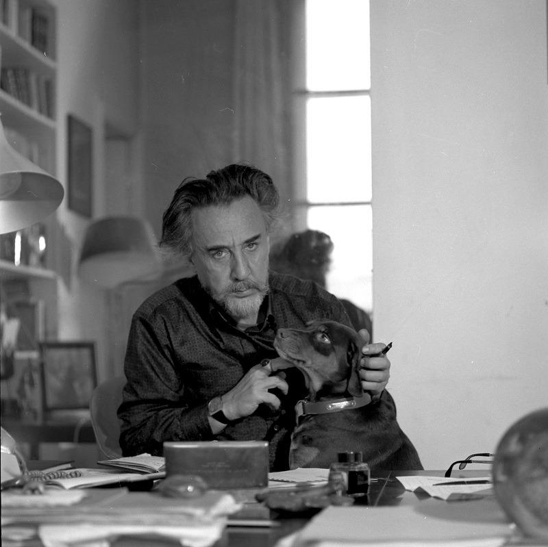 Romain Gary at desk, with dog