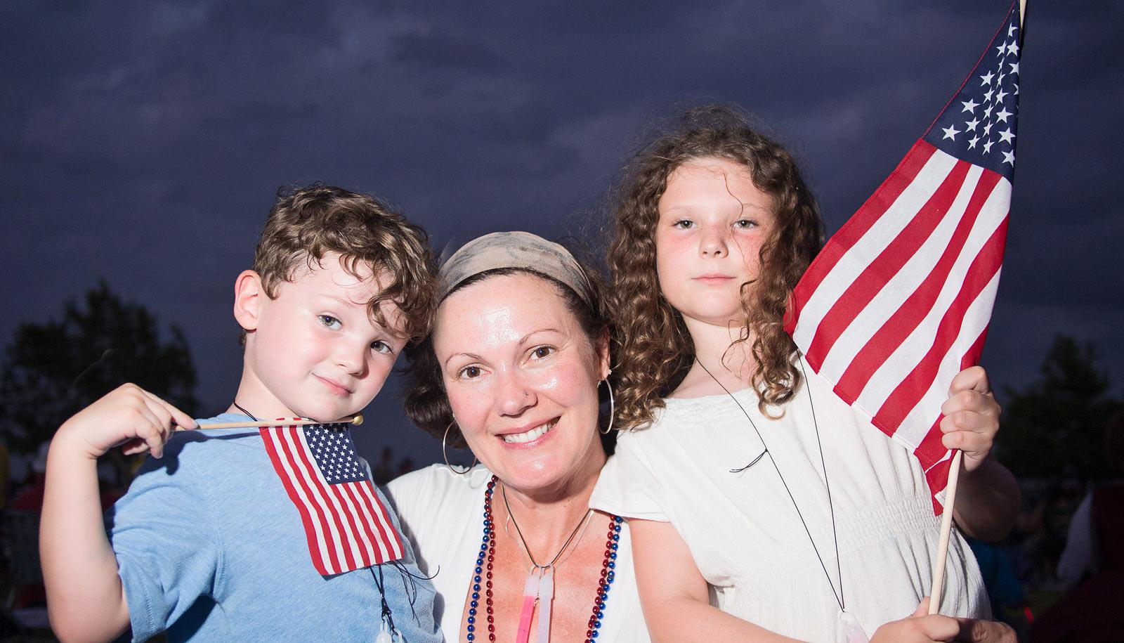 woman and two children with US flags