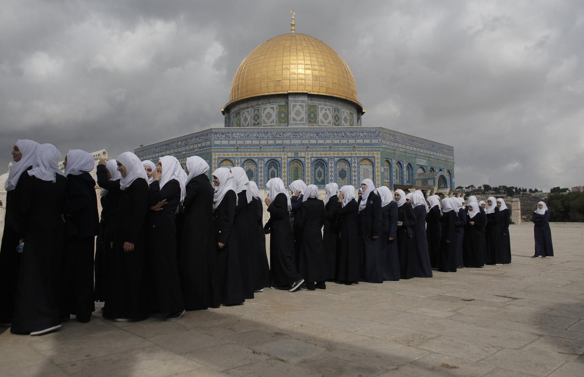 Palestinian school girls walk in line past the Dome of the Rock at the Al-Aqsa mosque compound in Jerusalem's Old City on October 27, 2015. Israeli lawmakers on Sunday approved a new version of a nation-state bill that would demote Arabic as an official language.