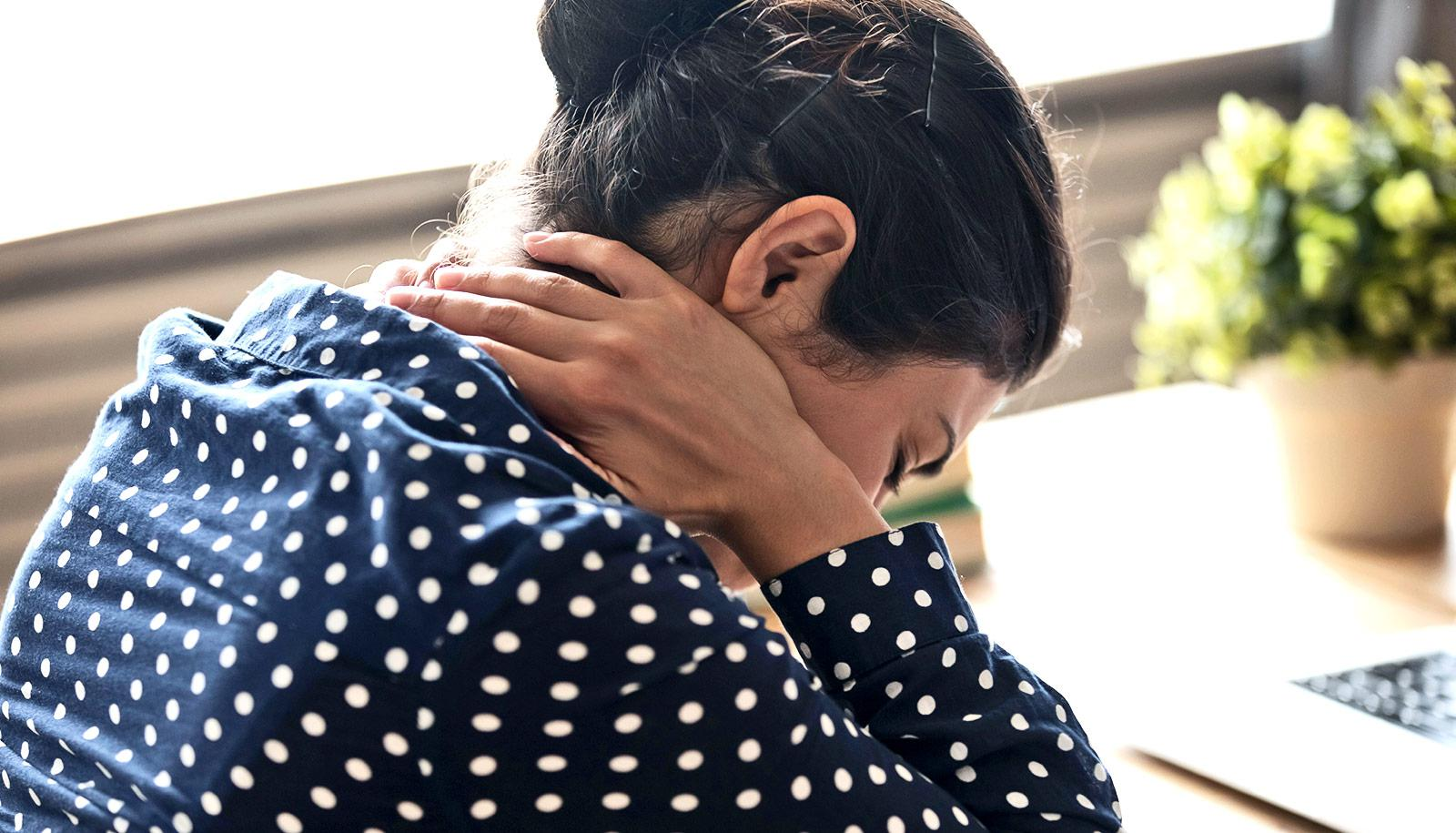 A woman at work holds the back of her neck while leaning down