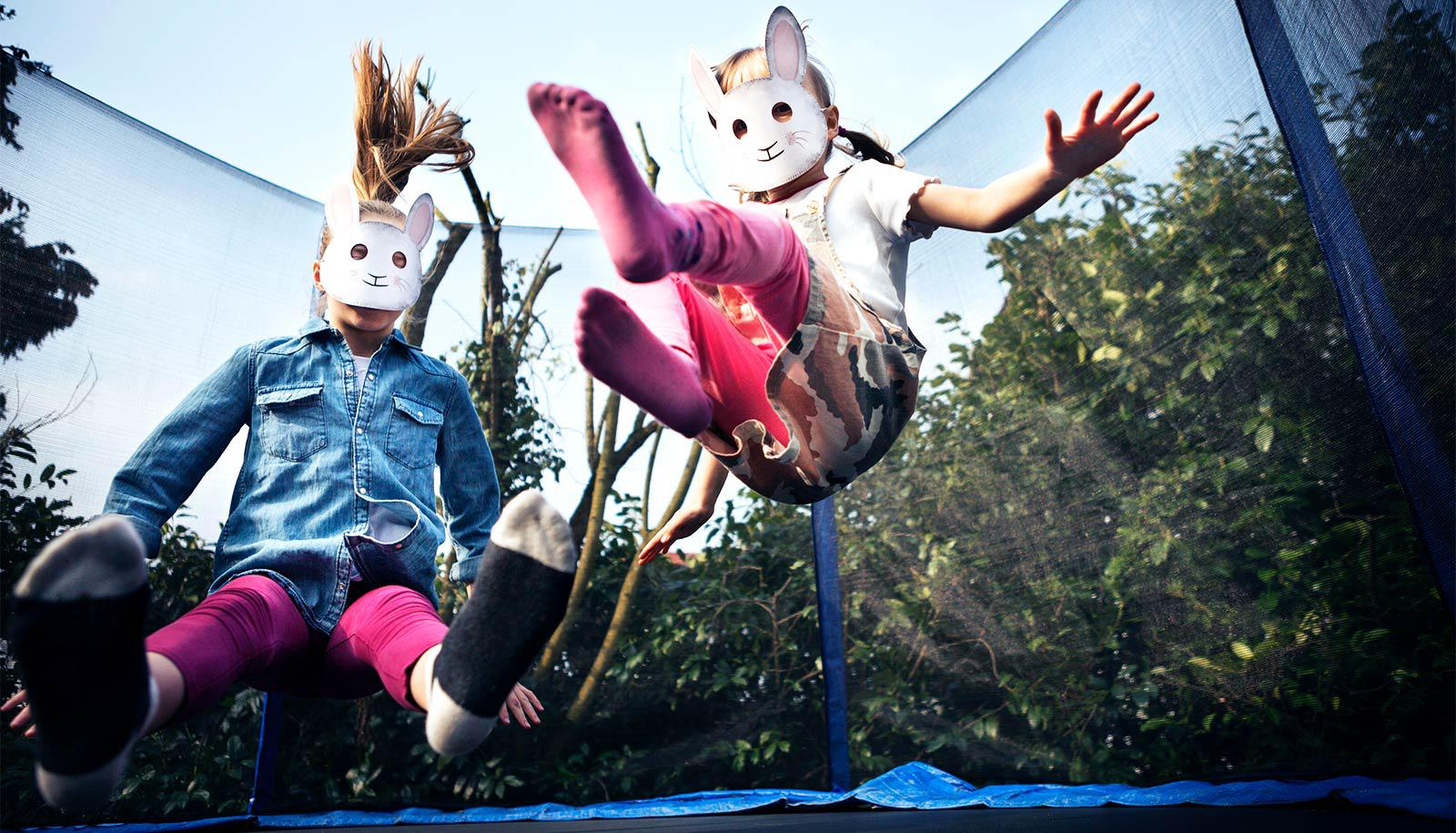 Two young girls in paper rabbit masks jump on a trampoline outside