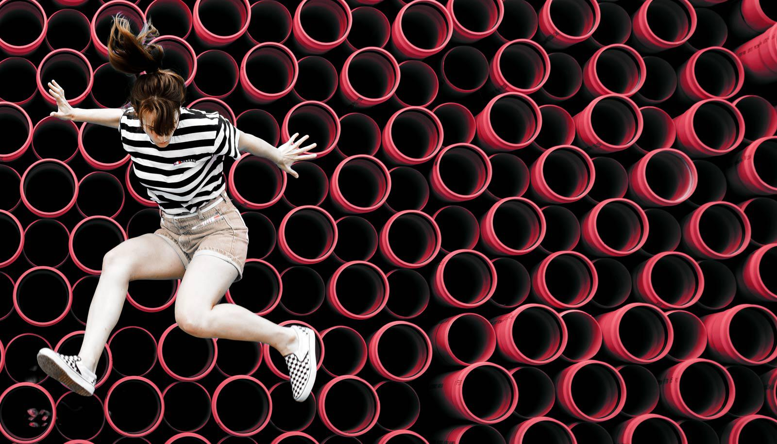 young woman on top of red tubes - blood vessels youth concept