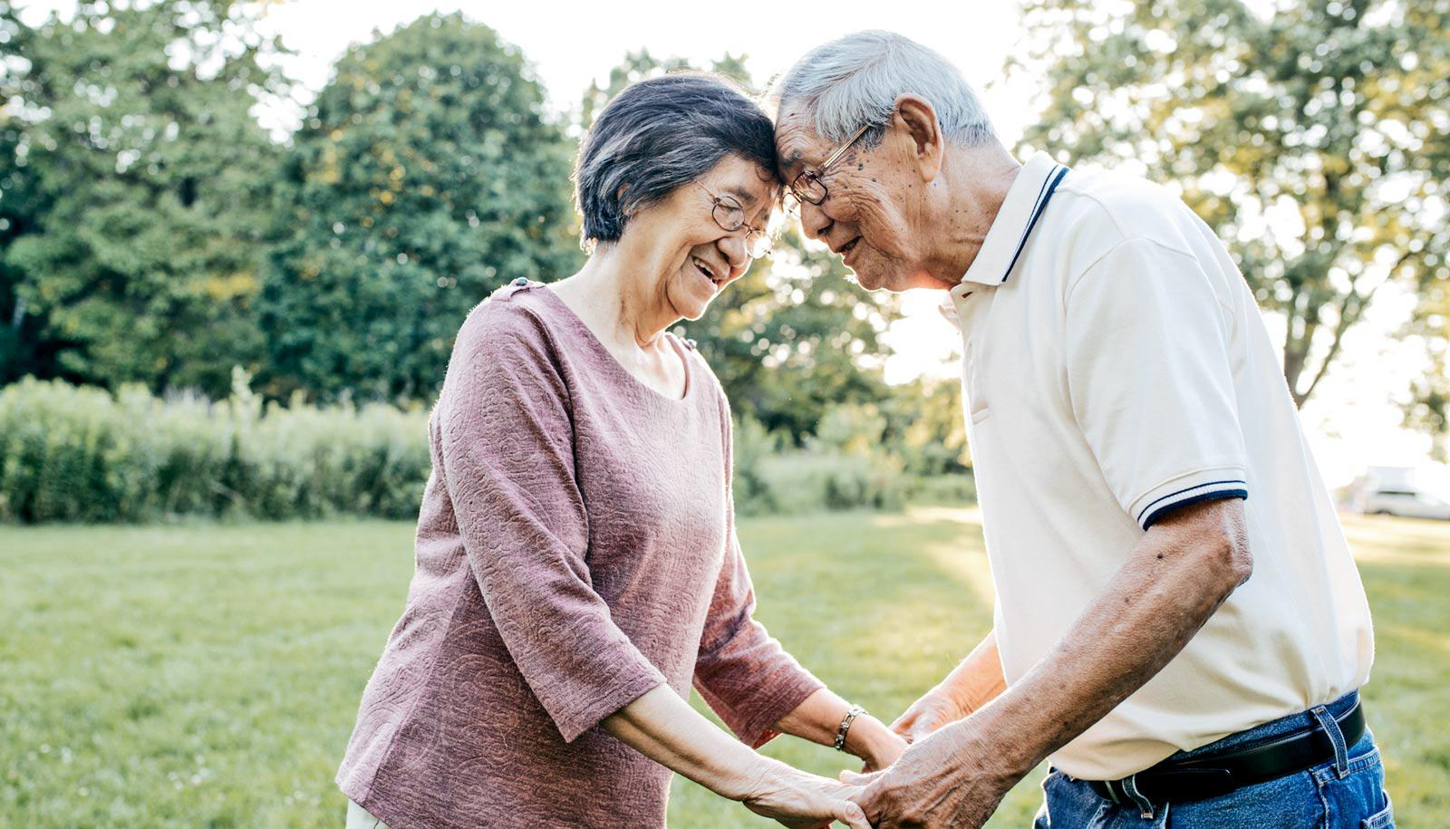 elderly woman and man touch foreheads outdoors