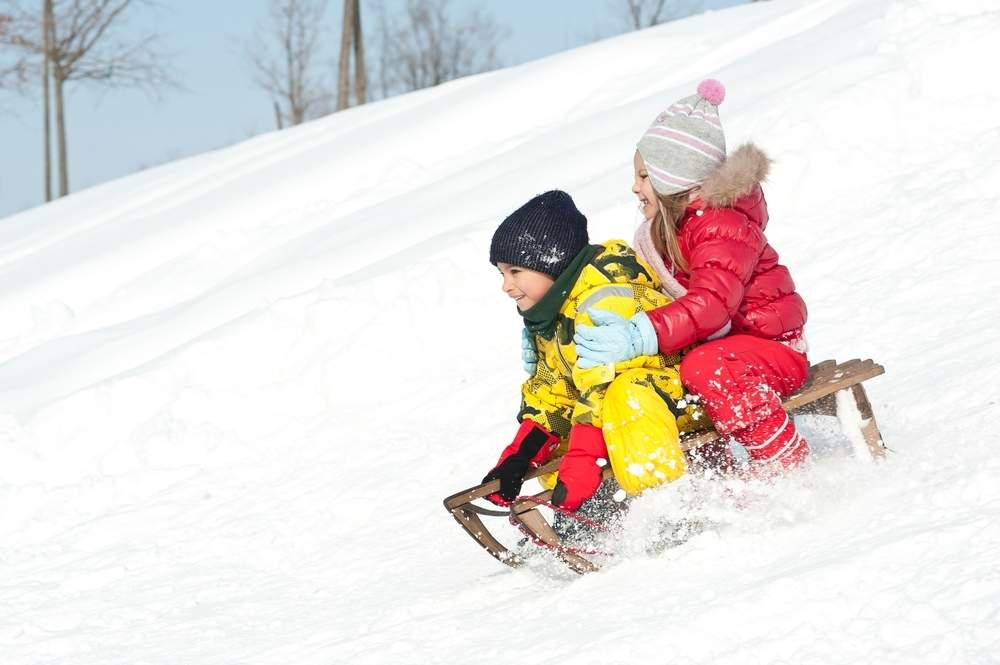 two children sledding downhill