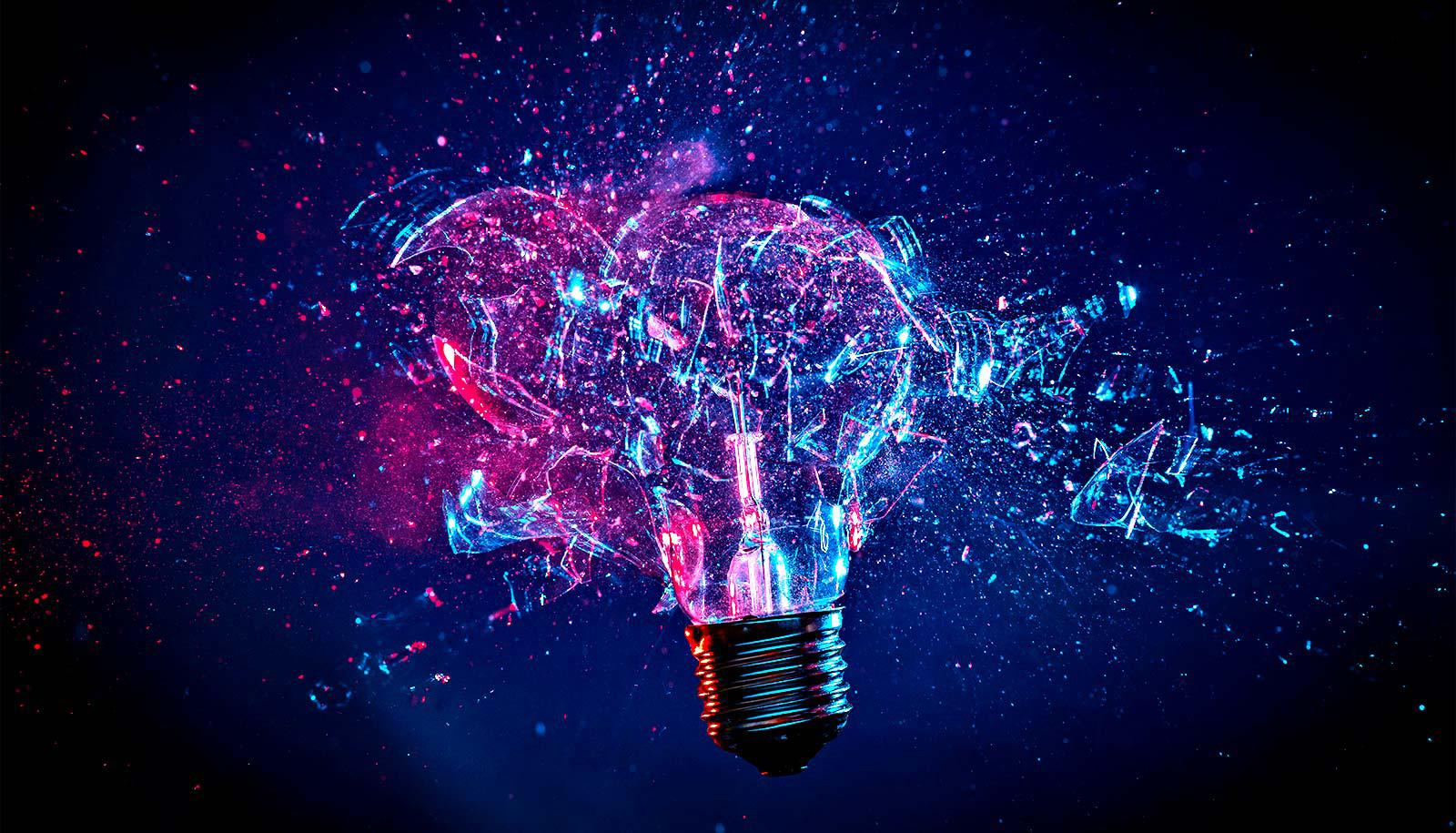 A lightbulb explodes with pink and blue light shining through it