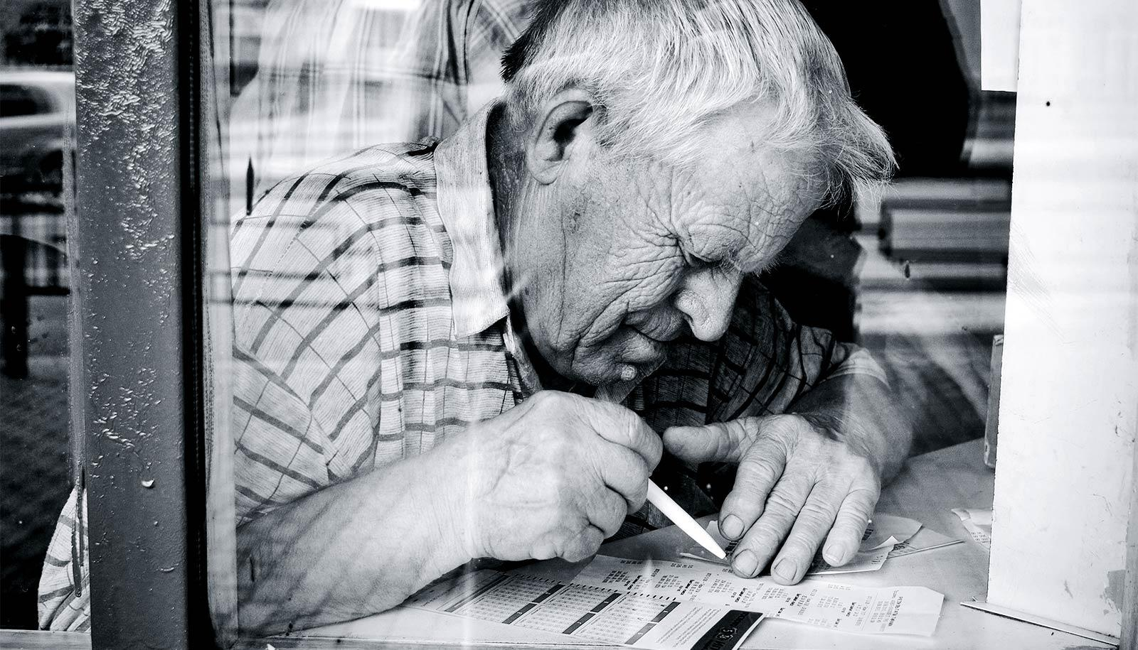 A man leans over a table as he uses a pen to check a lottery ticket