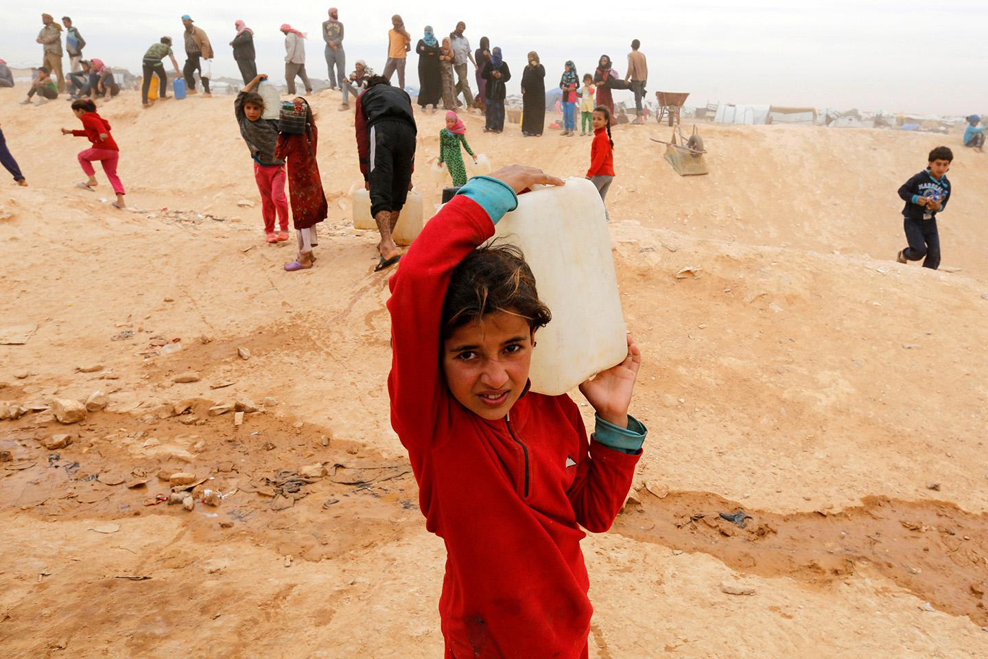 Syrian refugees collect water while after crossing into Jordanian territory, near the town of Ruwaished, east of the capital Amman, May 4, 2016.