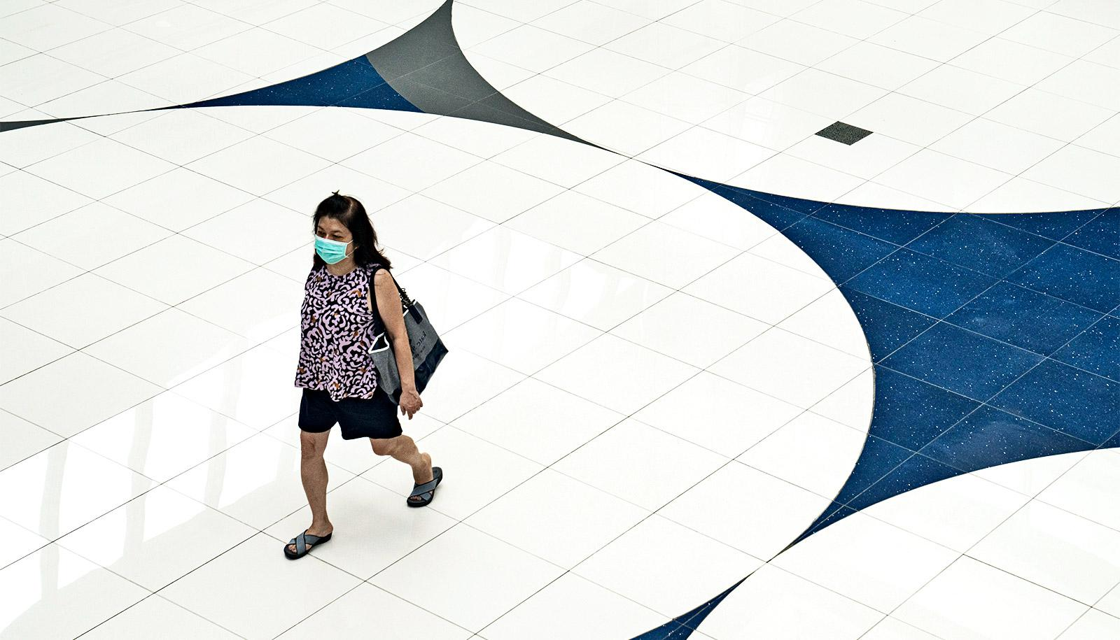 A woman walks over a white and blue tiled floor while wearing a face mask and carrying a purse