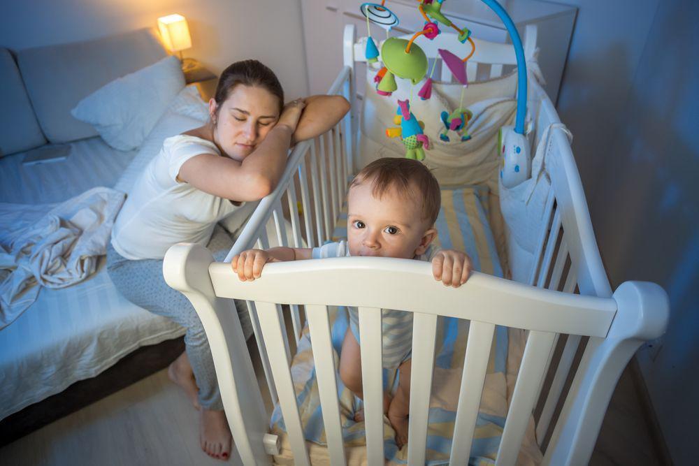 Mom Tired While Baby Is Awake Inside Crib