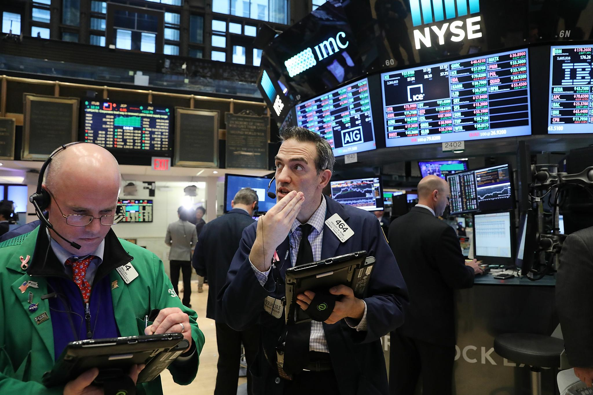 Traders work on the floor of the New York Stock Exchange (NYSE) as the Dow Jones industrial average closed above the 20,000 mark for the first time on January 25 in New York City.