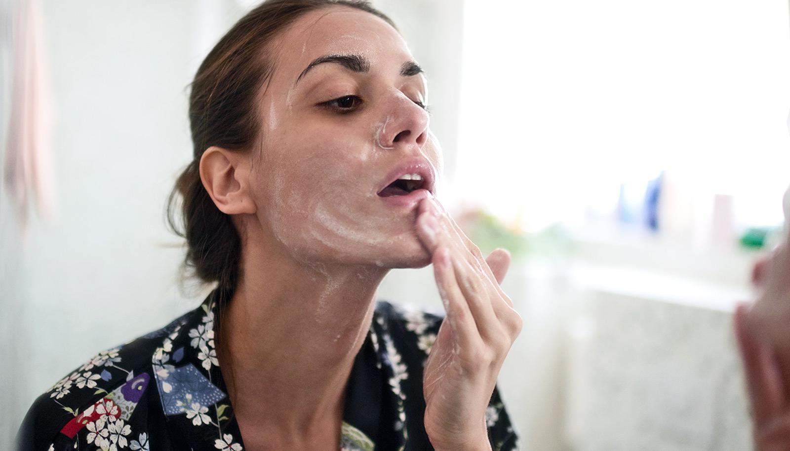 A woman rubs a skin cream onto her face