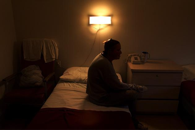 A resident sits on her bed at Oceanview Manor, an adult home in Brooklyn, New York, in September 2001. Three years ago, a federal judge ordered residents be moved out of adult homes like Oceanview Manor. (Nicole Bengiveno/The New York Times/Redux Pictures)