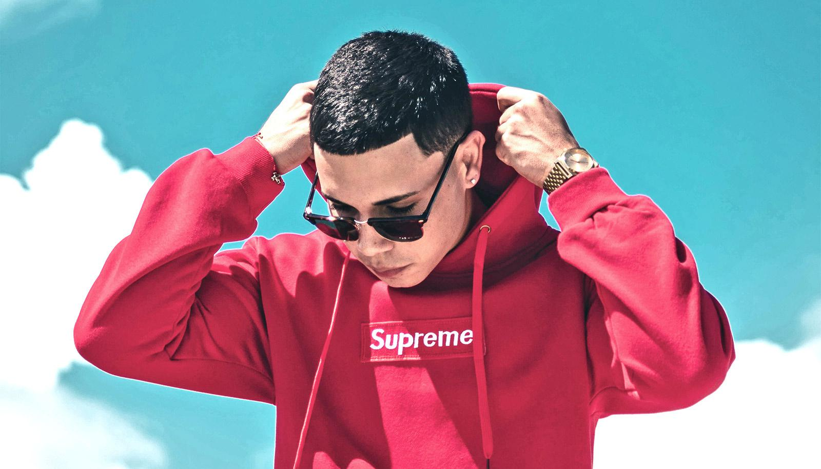 young man wearing Supreme hoodie (brands concept)