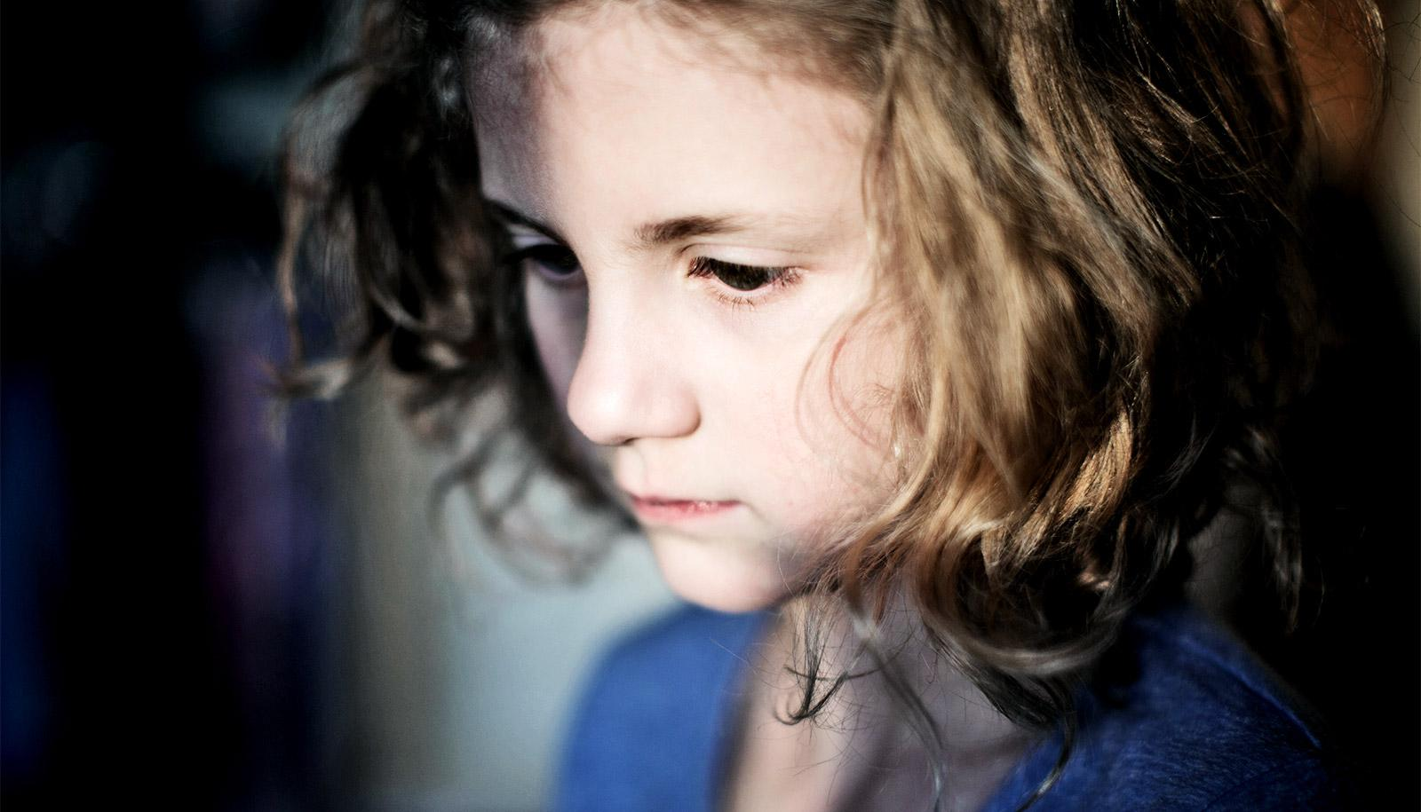 A young girl looks downward in sadness or deep thought with some of her face covered in shadow