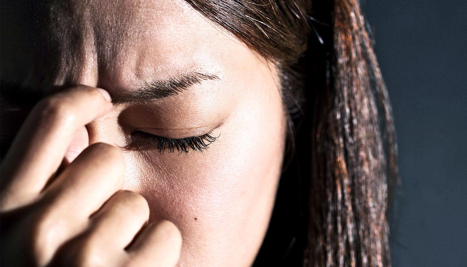stressed woman with eyes closed (debt relief concept)