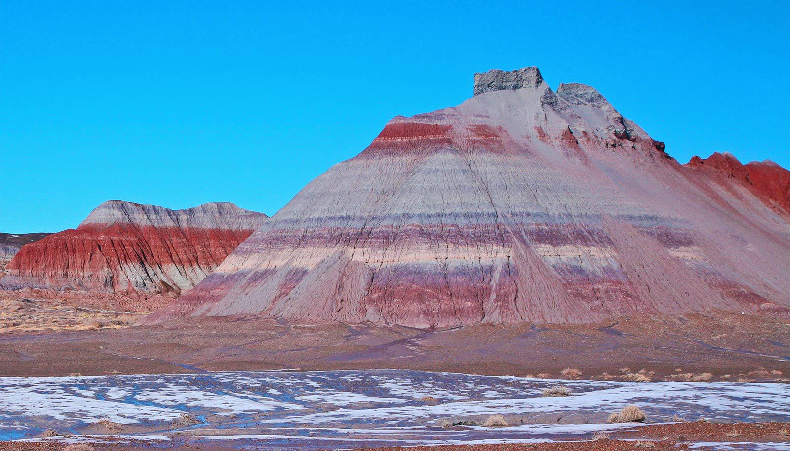 Red rocks can be seen in streaks on large, rocky hills