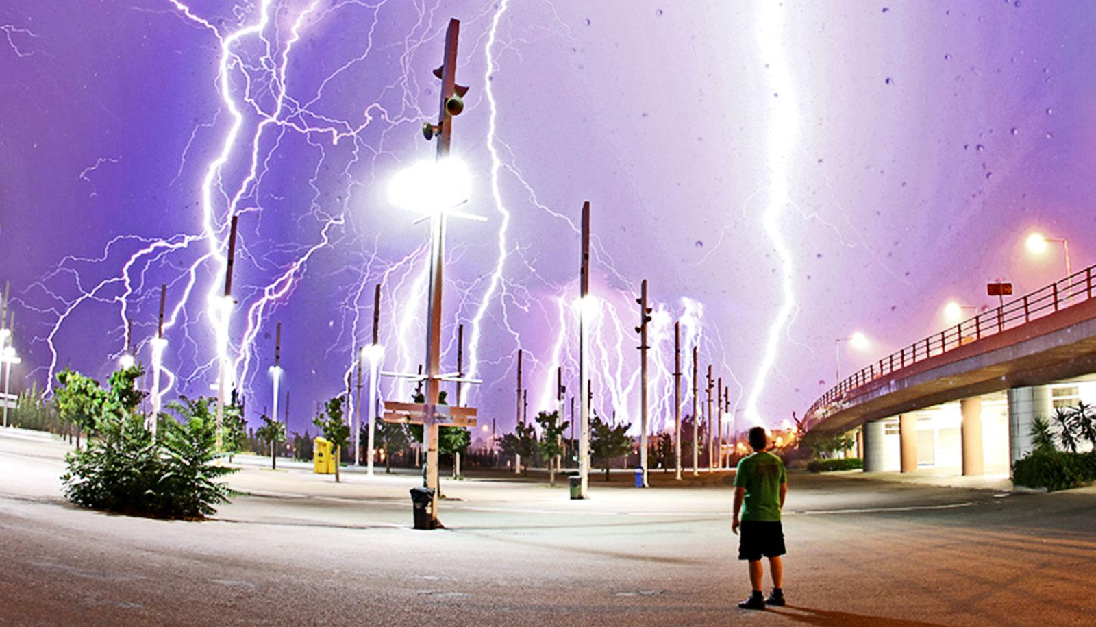A man looks up from a parking lot to see a purple sky filled with white lightning
