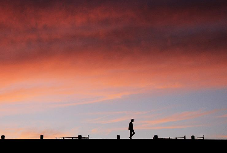 Think You Can't Meditate? 3 Styles of Meditation to Satisfy Any Skeptic by Lori Bloomfield. Photograph of a man's silhouette against a colorful sky by Islam Hassan