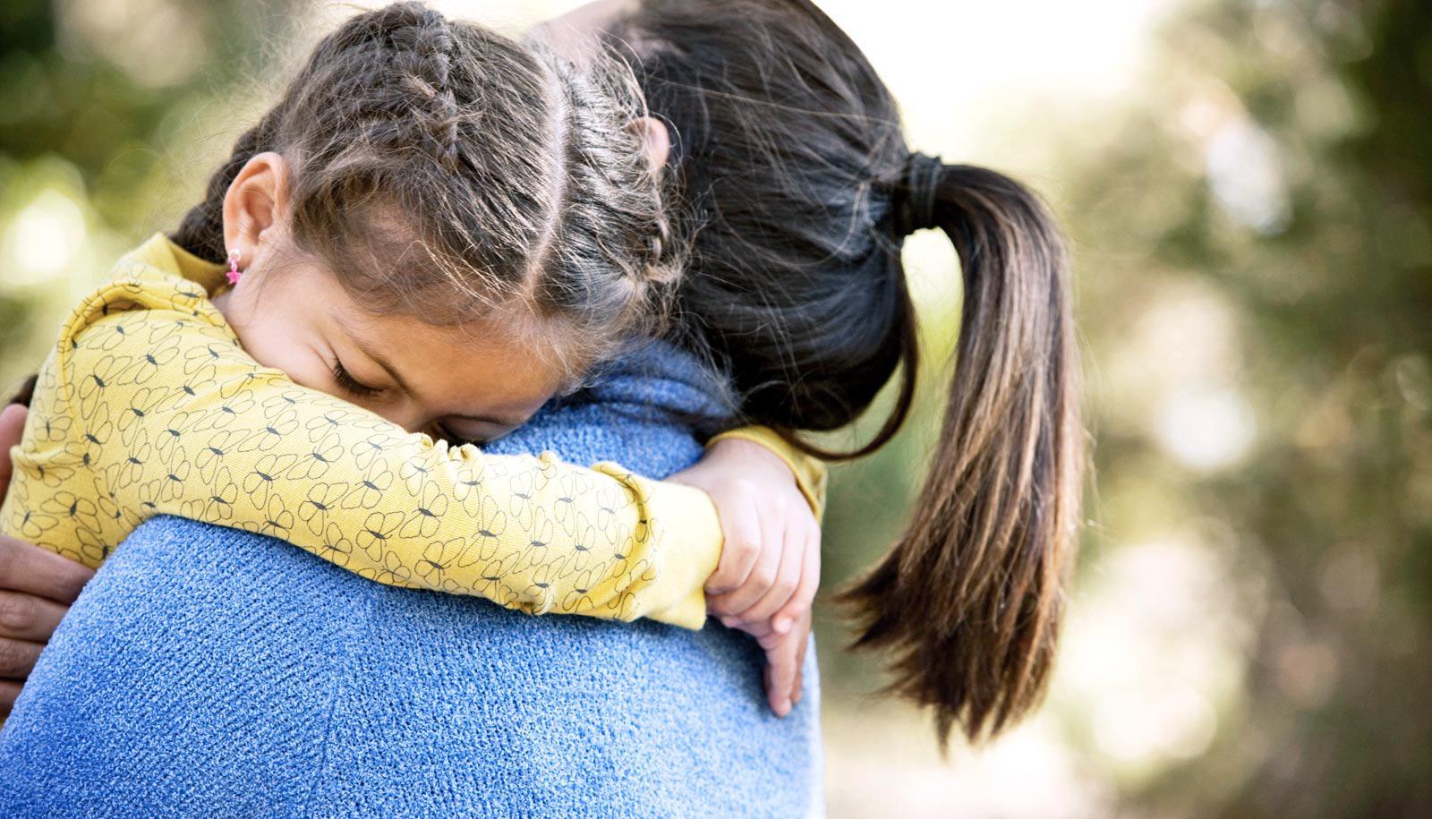 daughter hugs mother facing away