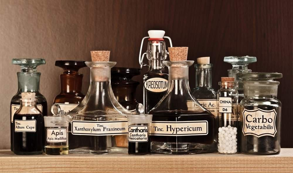 glass bottles on a shelf with handwritten labels