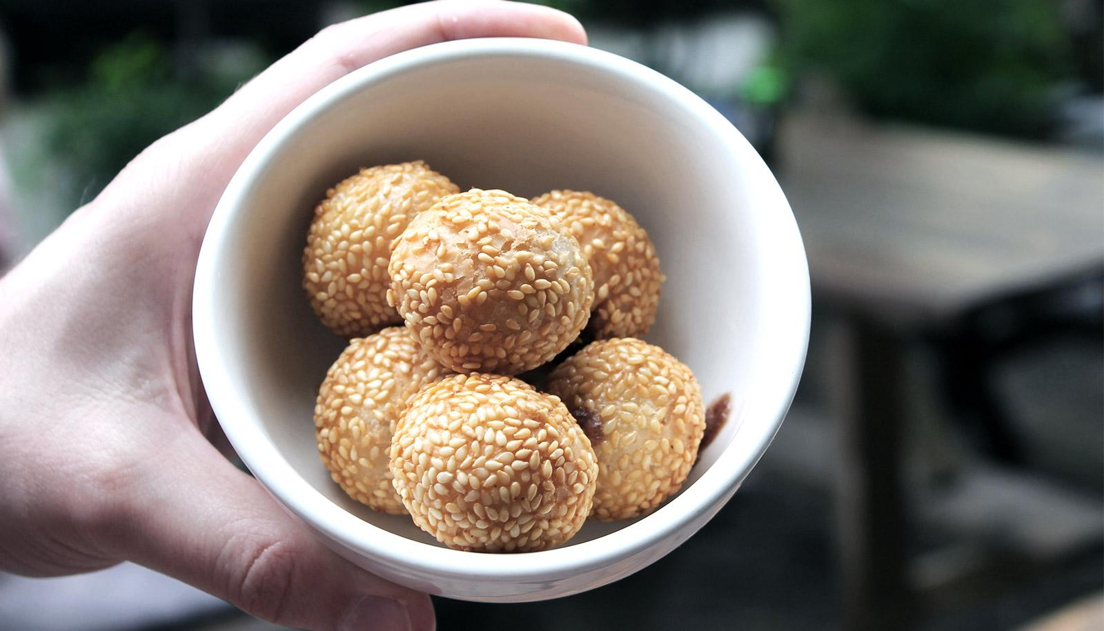 The image shows sesame balls in a white bowl. (sesame allergy concept)