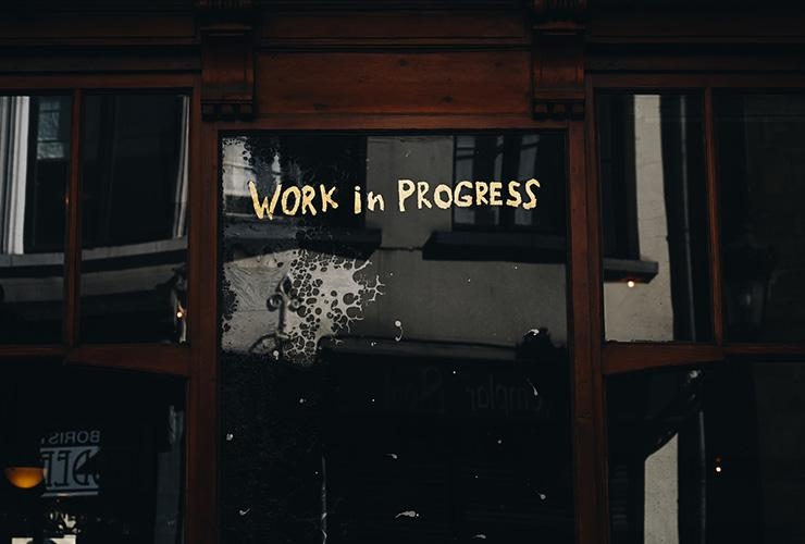 "Perfectly Imperfect: Saying Goodbye to The Curse of Perfectionism by Laurence Favier. Photograph of a building door with ""work in progress"" written on it by Gaelle Marcel"