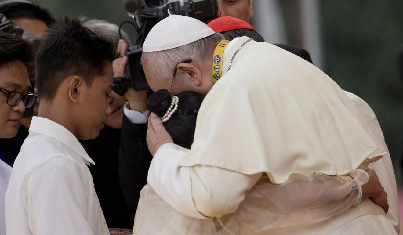 Pope Francis hugs two former street children during his meeting with youths in Santo Tomas University in Manila, Philippines. Photo: AP