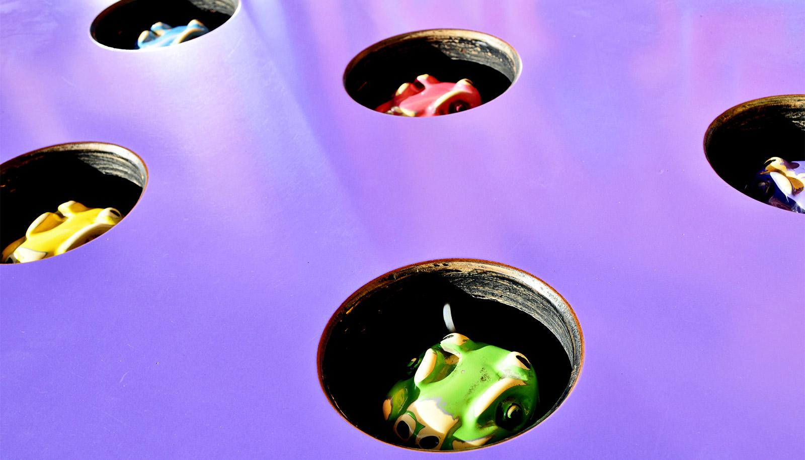 "Brightly colored animal figures peek out through holes in a purple ""Whack-a-mole"" table"
