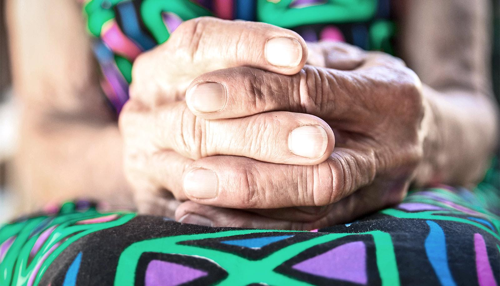 older woman's hands on colorful dress (rapamycin concept)