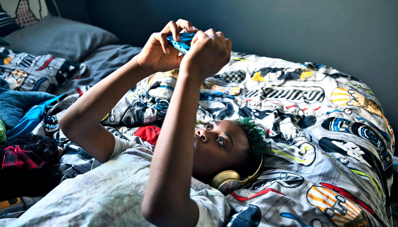 A young teen boy lies on his bed (covered in skateboarding-themed blankets) while playing a game on his phone and wearing headphones