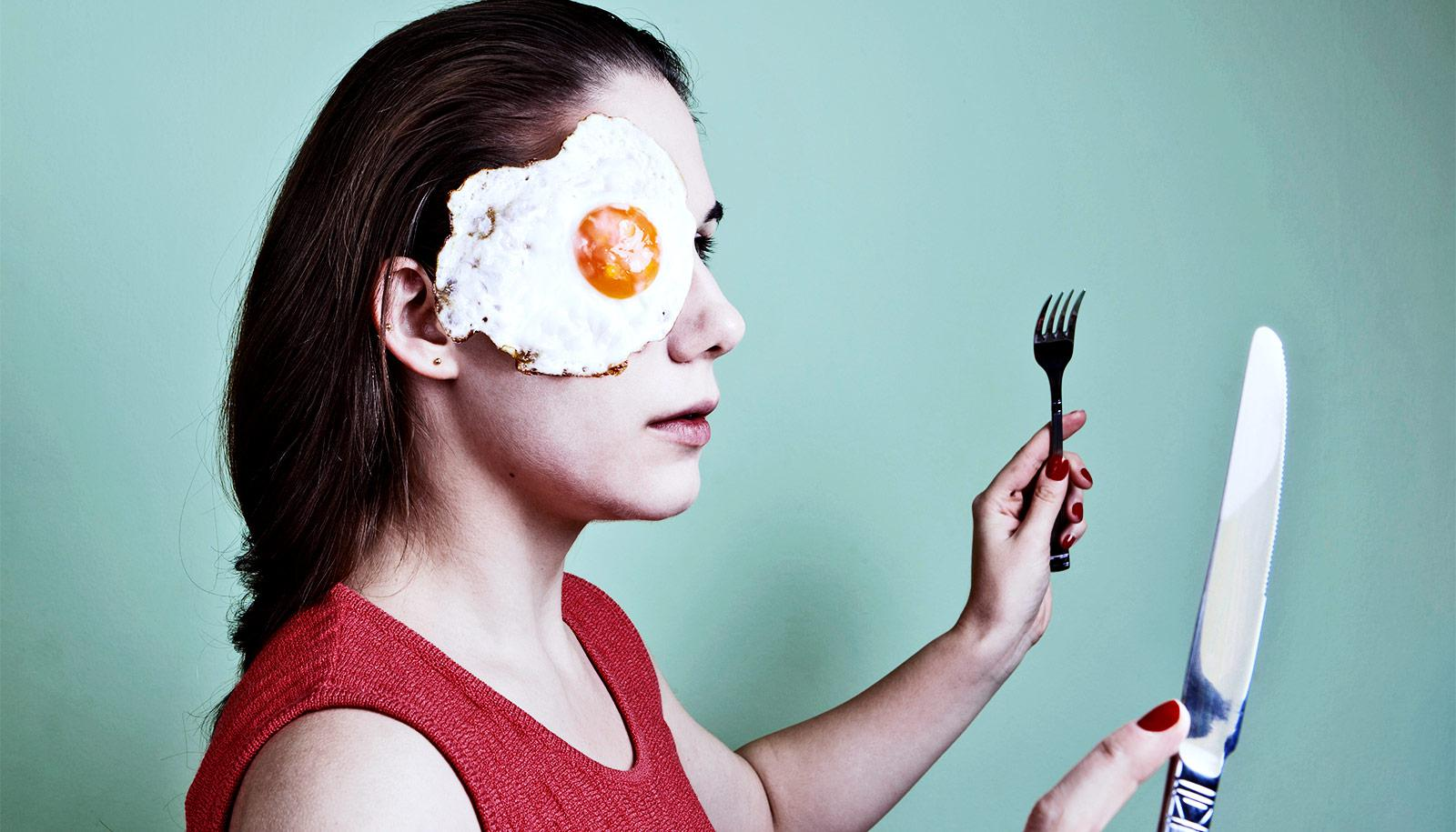 A young woman in red holds a fork and knife up while a fried egg hangs on her face
