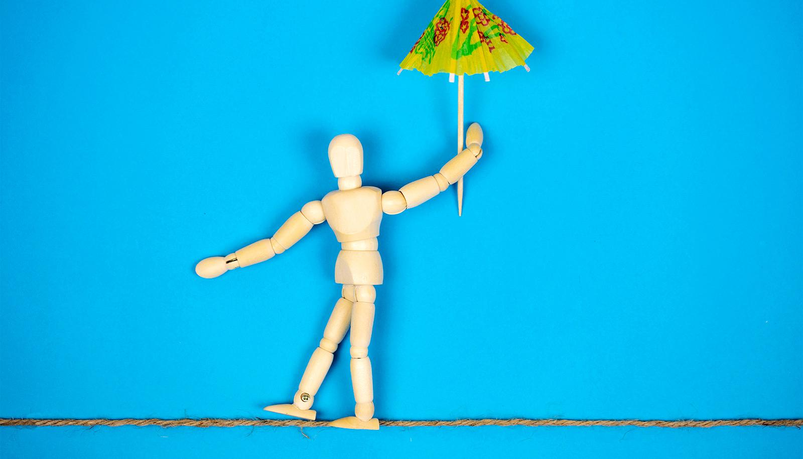 A wooden anatomy figure looks like its walking a tightrope while holding a cocktail umbrella