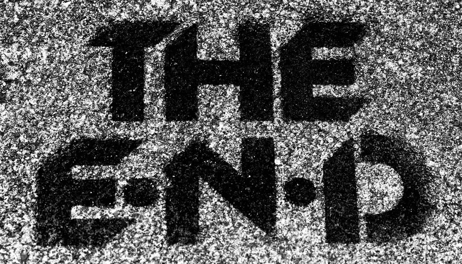 """Painted text on asphalt reads """"The End"""""""