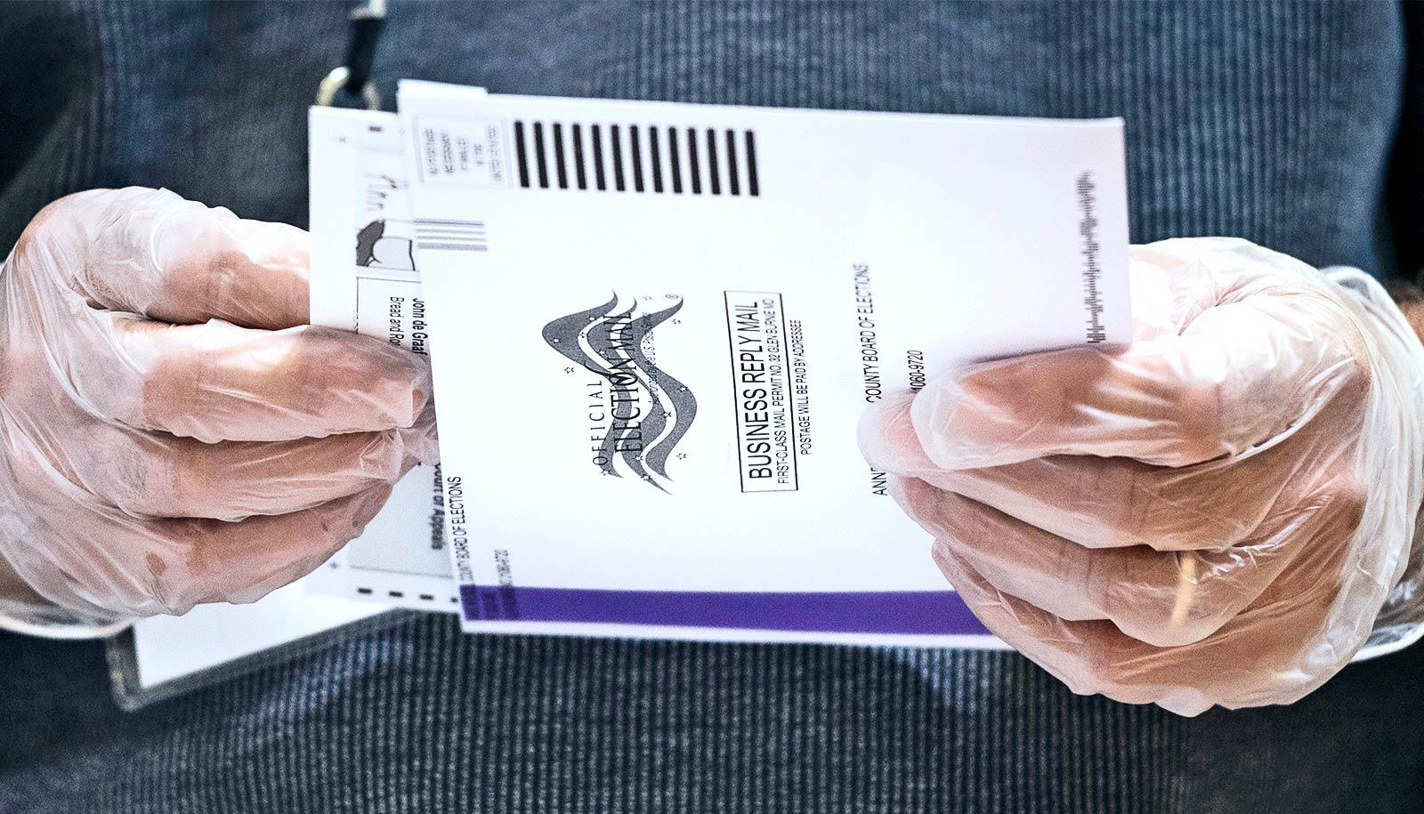 An election worker opens a mailed-in ballot