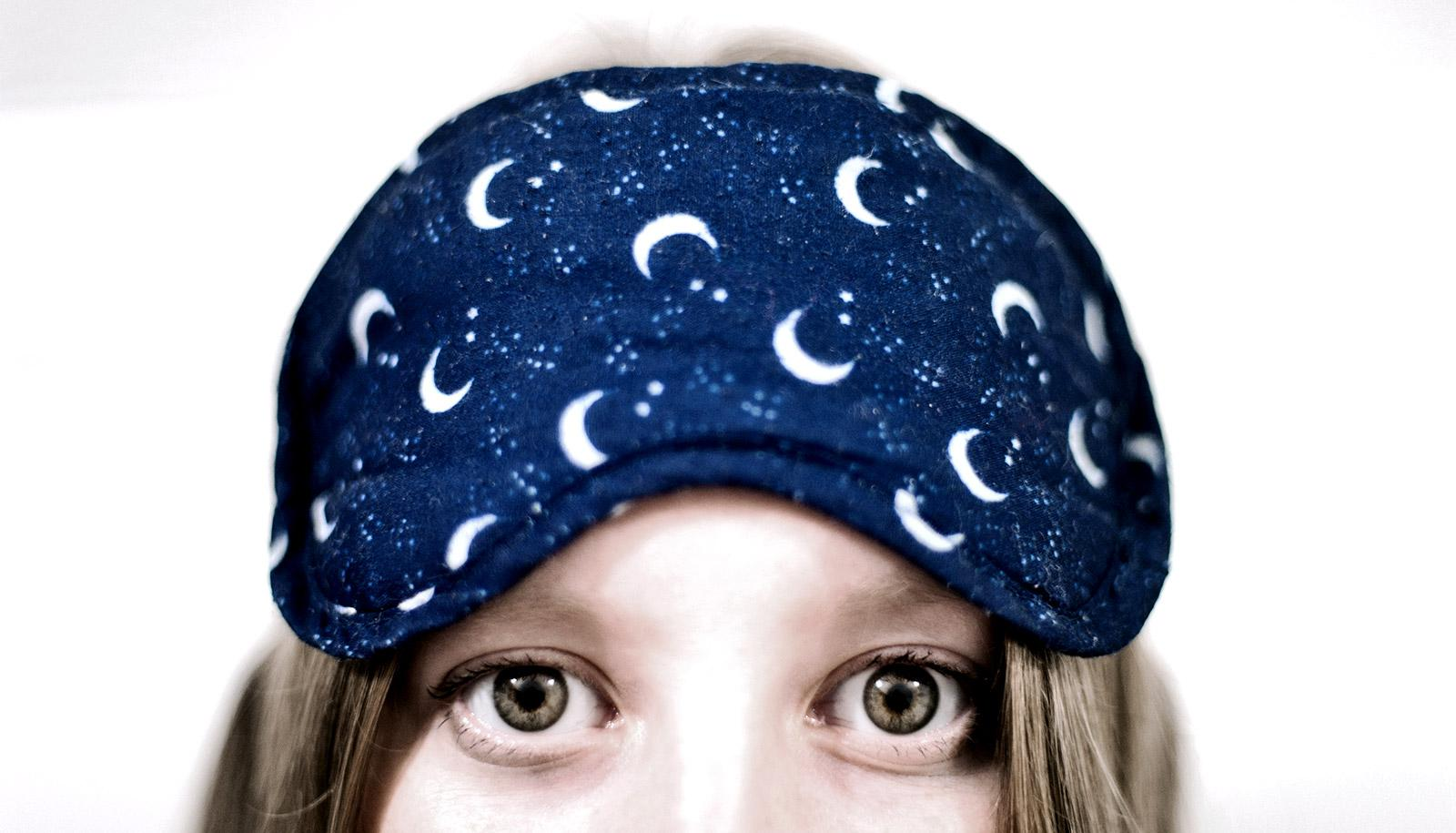 A woman wears a sleep mask on her forehead while her eyes are wide with insomnia