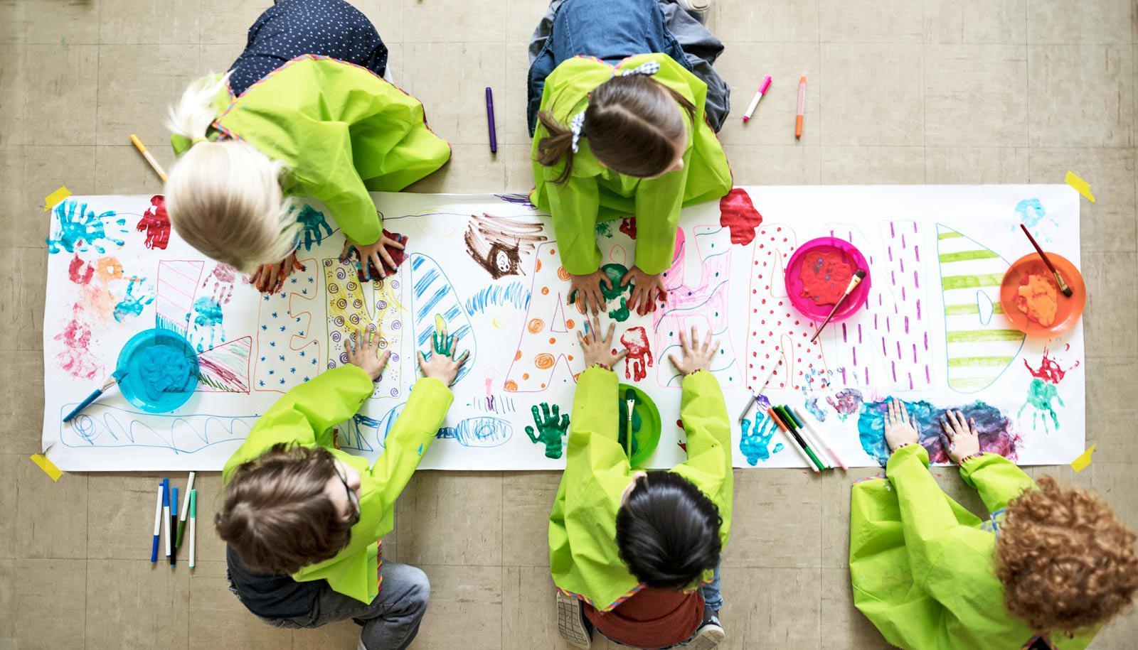 five kids in green smocks paint